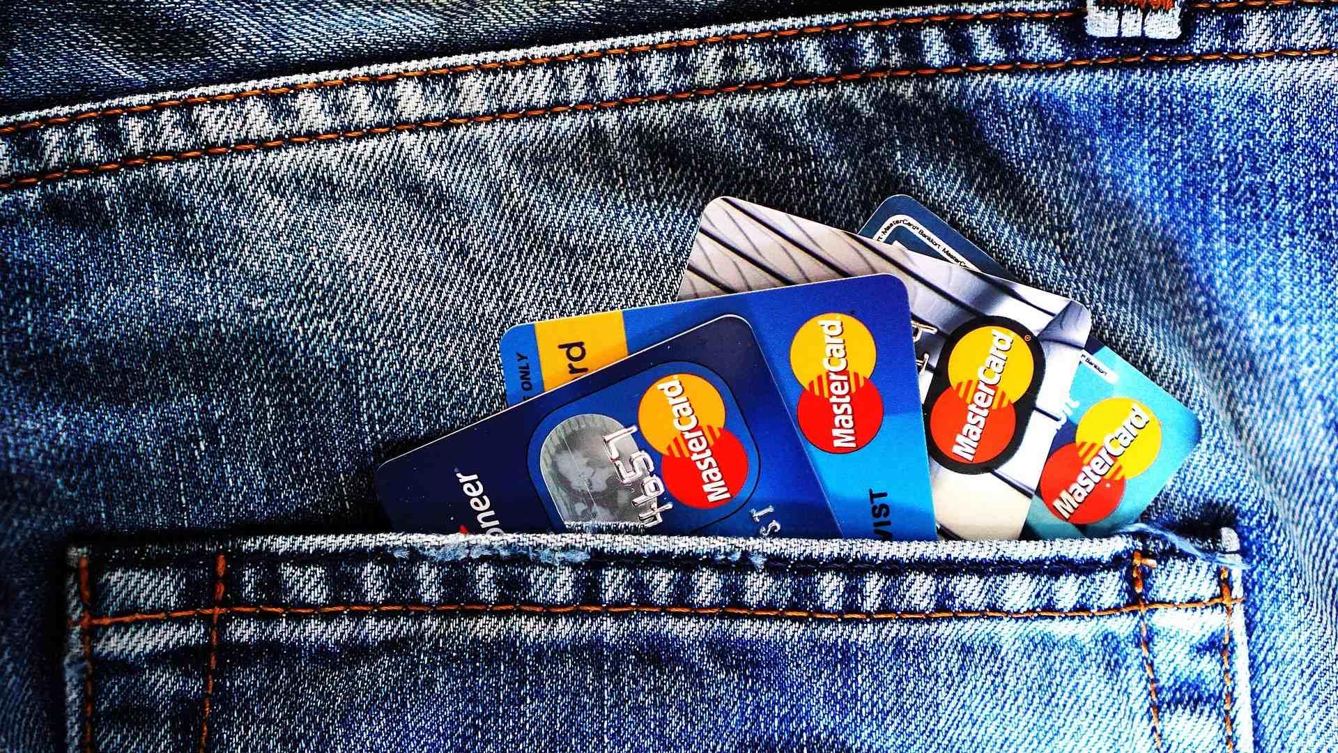In der hinteren Tasche einer Jeans befinden sich vier Kreditkarten von Mastercard